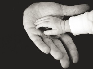 baby touching man's hand